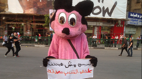 "The dishevelled Mickey Mouse costume, worn by a regime supporter. The sign reads ""Sisi does not need to take an oath because the people trust him."" Tahrir Square, Cairo, 8 June 2014 (the day of Sisi's coronation). Photo by Amro Ali‬‬"